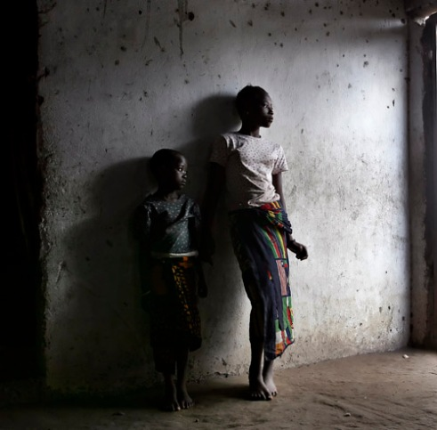 Amelia, (R) and her sister Mamdiuana, live alone, orphaned after both parents died from the AIDS virus in a small village near Mambone, Mozambique. (2005)