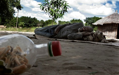 Arlindo, suffering from chronic HIV and unable to walk lies near a bottle of natural herbs he uses to relieve his pain. Arlindo lives in small village on edge of Vilankulos, Mozambique. (2005)