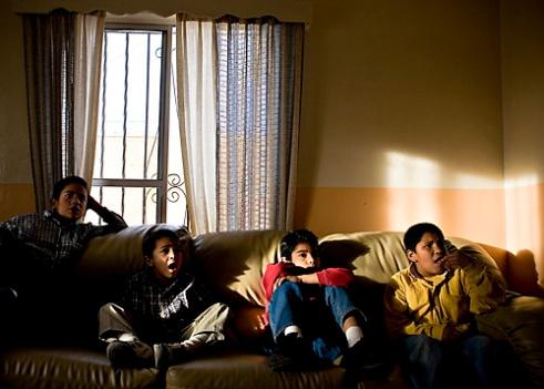 Fernando Figueroa, 10, Sergio Valesquez, 6, Rigo Montaño, 9, and Eulogio Felix, 9, watch Lucha Libre, or Mexican-style wrestling on television.