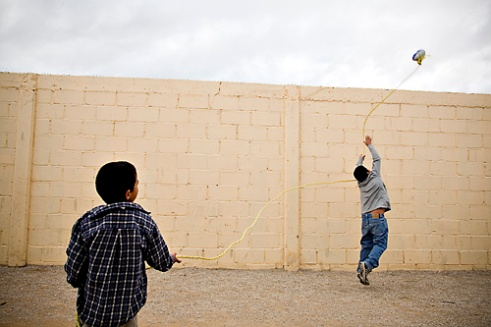 Sergio Valesquez, 6, and Eulogio Felix, 9, play with a rope and a football, tossing it over the wall and pulling it back over again and again