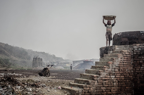 A worker on top of one furnace .Wasteland in Kolkata,India.