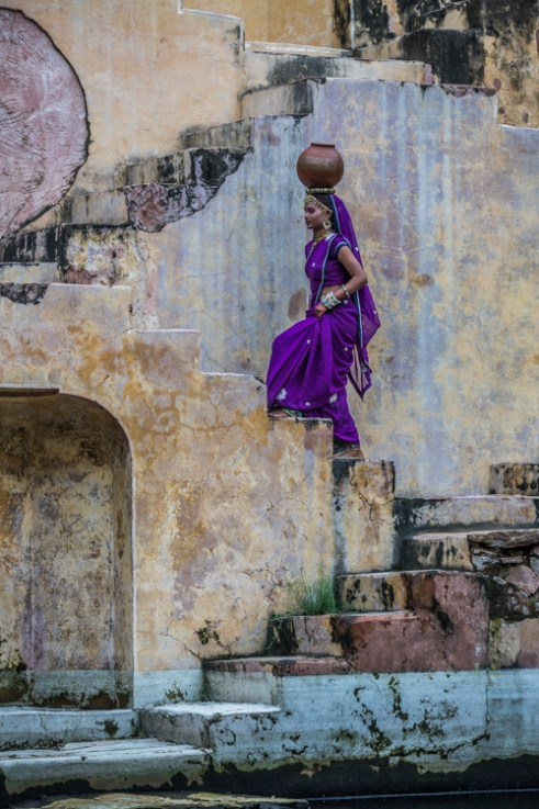 A young woman collects water from her local stepwell Jaipur, India