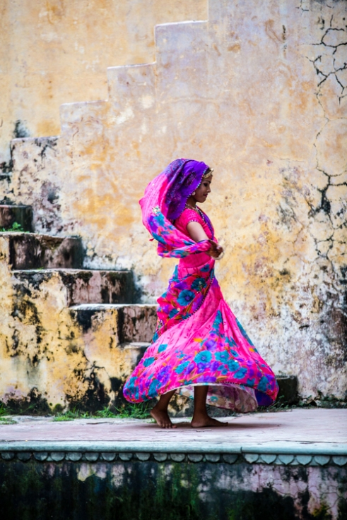A young woman pauses for a dance whilst her older sister collects water from their local stepwell Jaipur, India