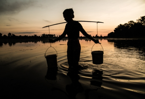 A young woman collects water for her family as the sun rises Siem Reap, Cambodia