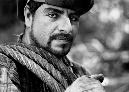 "Raul Mora Avalos - is a Hook Tender on a high lead logging operation. His answer to my question, 'What do you like most about working in the woods?' was ""When I get home and my little girl runs and jumps into my arms and says, 'Hello sweet daddy'."" Near Fort Bragg, California, 2004"