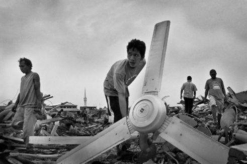 Man searching rubble of his former home. His house was on land evicted by local authorities due to overcrowding and declining soil content area. Luar Batang, Jakarta. Indonesia 2016