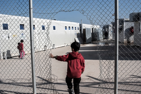 VIAL Refugee Detention Center Chios - Greece | The inhabitants of the center have made holes in the fences in order to provide more freedom of movement for themselves. The center is surrounded by land owned by farmers. Many of the refugees/migrants use this land for a sense of space and freedom and to use it as a toilet.