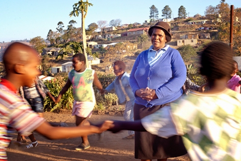 "Khonsiwe Meyiwa, 57 years, Inchanga, Valley of 1000 Hills, KwaZulu-Natal Khonsiwe came to Inchanga in 1994 due to political violence in her home town of Swayimane, near Wartburg in KwaZulu-Natal. After she was widowed in 1999, she was driven to start a crèche and after-school club when she learnt that a child nearby had died from neglect. Caring for seven of her own children (and 13 grandchildren), she has dedicated her life to helping children and parents in the community. Khonsiwe founded the Hillcrest AIDS Centre Trust's (HACT) very first Gogo Support Group, and set up her own adult education school. She has just qualified for her first, full time paid job as a Child Support Worker with HACT, running a Support Group focused on HIV prevention and life skills for 50 children. She says, ""I never finished school so decided to educate myself and got my certificate aged 54. If I can educate myself at my age, so can others - fifteen parents at the school now have certificates."""