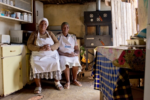 "Nokuthula, 42 years & Busisiwe, 52 years, Valley of 1000 Hills, KwaZulu-Natal Nokuthula and Busisiwe are sisters and members of Khuthalani Support Group in KwaNyuswa. The lively, enterprising group set up a community bakery and pizzeria not long ago, having sourced the funding themselves through a private company social enterprise (Mama Mimi). The company provides the bread mix, the materials and training, receiving a small share of the sales. The wood burning ovens, which were sponsored by corporates, produce 25 loaves a day which the Support Group sells at community events and from their little corner shop with much success. ""We were just home alone before with our children and grandchildren and no income. The bakery gives us everything we need and keeps us busy."""
