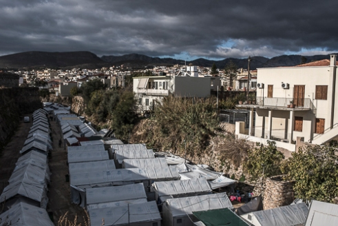 """Souda Refugee Camp, Chios - Greece.   On the 18th of november 2016, a far-right mob attacked the volunteer run Souda camp (seen on this photo). The assailants threw petrol bombs, fireworks and stones and assaulted some of the volunteers leaving some injured and damaging one of the tents. The Aegean islands are home to around 10 000 refugees and migrants from all over the world. Since the `EU-Turkey Refugee Deal` the influx has been decreased but not stopped. This causes tensions to a part of the Chios population and the refugees/immigrants. A German couple who owned a holiday house on the eastern part told me """"In the beginning they would come and go quickly so we helped them. Now they are staying, we don't want that""""."""