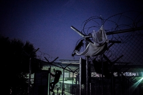 VIAL Refugee Detention Center Chios - Greece   The fences of VIAL also have a rather practical purpose: hanging clothes. Here a young Syrian girl is gathering her families clothes.
