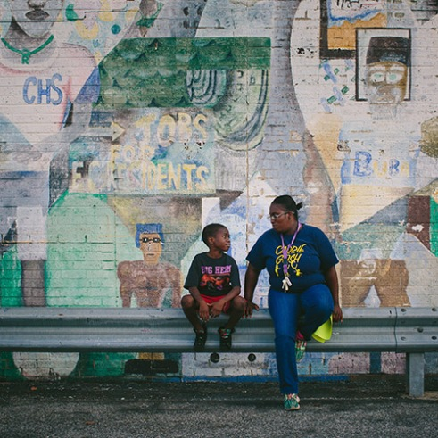 "East Chicago, Indiana Nayesa Walker and her 7-year-old son Kash Lott wait for a school bus to drop off his two younger siblings at the West Calumet Housing Complex. As a child, Walker helped create the mural that covers the neighborhood's community center. Walker and other residents tried to stop the neighborhood's demolition. ""We feel like we're just being thrown out,"" Walker said."