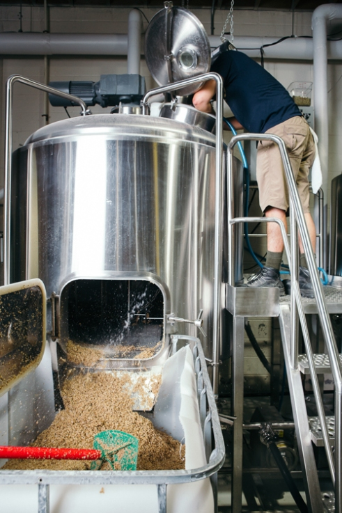 Durham, North Carolina - Wednesday July 7, 2016 - Ponysaurus Brewmaster Keil Jansen sprays out the mash while cleaning out the grain used while brewing their Rye Pale Ale Wednesday morning at the Ponysaurus in Durham, North Carolina.