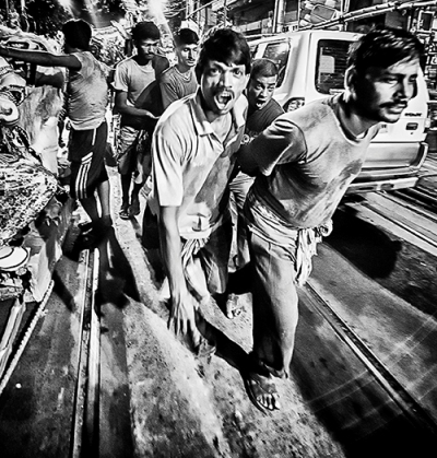 Kumartuli The roar of the laborers as they dragged the heavy idols, the screeching of the rollers of the trolleys that carried it, the chants of the people who had come to take their Mother home, broke the deadly silence of that night.