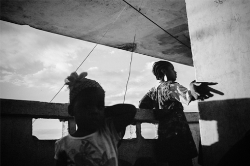Children play on the balcony of a concrete building