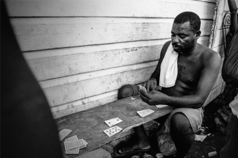 Two men play cards in a narrow side street close to a neighbouring quarter that is controlled by an opposing gang