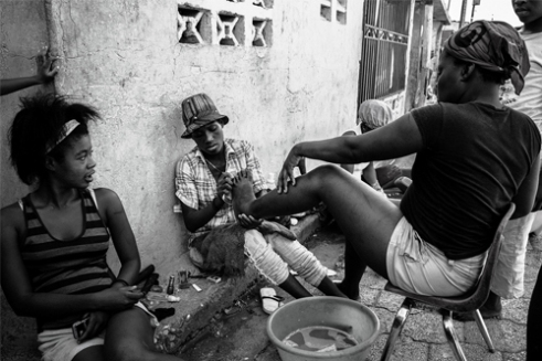 Women pedicure their feet on one of the main roads of their quarter inside the mega-slum