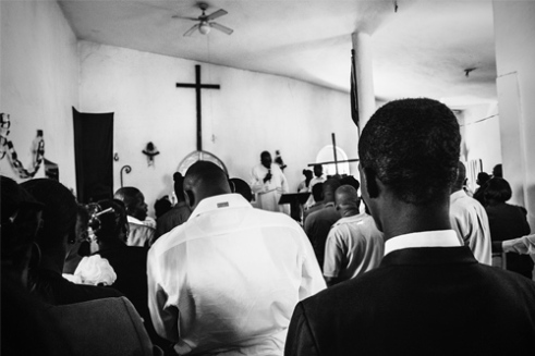 A child from Cité Soleil gets baptised in a church outside of the mega-slum, which prevents the father from attending the ceremony as he is wanted by the UN and the Haitian police.