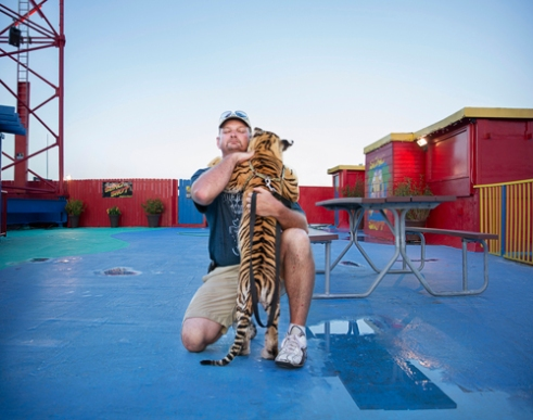 "Jody with ""Animal Adventures"", a sanctuary based Okeechobee Florida, is depicted embracing his tiger cub named Dahlia at the Daytona Beach Boardwalk and Amusement area in Florida, where he was selling encounters to ""play and pet"" the cub for $25.00. The appeal and accessibility of cub encounters are rarely scrutinized. This particular cub encounter was located between a loud ""Slingshot"" ride and roller coaster, where Dahlia was made to pose for pictures with paying customers 12 hours a day for a week under these stressful conditions. It is illegal to sell encounters with big cats after they are 40lbs. under Florida law. The 5-month-old cub in poor health was above the weight limit for these standards, which poses a danger for her as well as the public. 2013."
