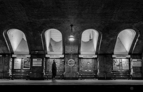 The famous baker street tube station with a gentleman that could be from the sherlock homes novels walking through